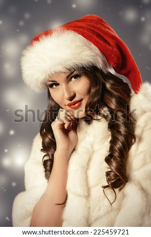 Happy beautiful woman in white fur coat and Christmas hat posing at studio. Winter holidays. - stock photo