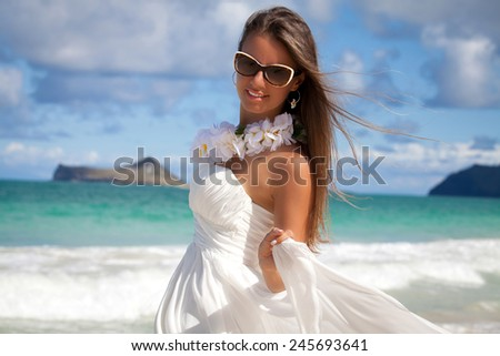 Happy beautiful woman in white wedding dress on a Hawaiian beach in paradise. Luxury resort vacation. - stock photo