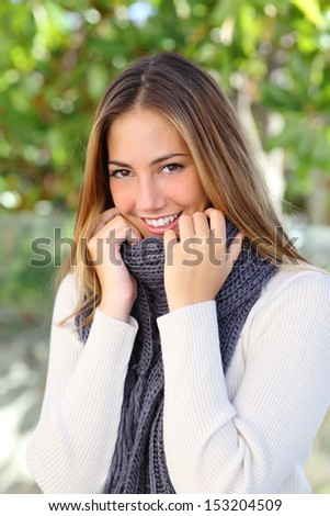 Happy beautiful woman keeping warm with a sweater and a scarf outdoor in a cold winter
