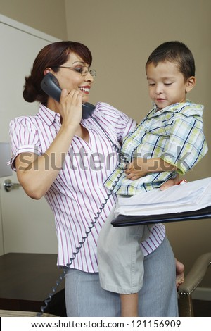 Happy beautiful woman looking at son while communicating on phone - stock photo