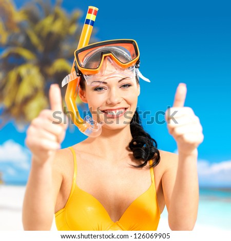 Happy beautiful woman on beach with thumbs up sign. Pretty girl with a protective swim mask on the head. - stock photo