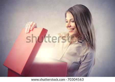 Happy beautiful woman opening a gift - stock photo