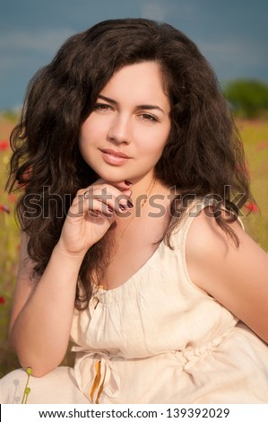 Happy beautiful woman resting in blossom spring garden with field flowers on nature looking happy smiling outdoors. Brunette girl on grass in park enjoying  life. Indian woman in country summer dress - stock photo