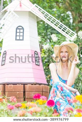 Happy beautiful woman sitting in a flower garden. - stock photo