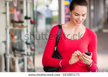 happy beautiful woman texting on a mobile or smart phone whilst out shopping. - stock photo