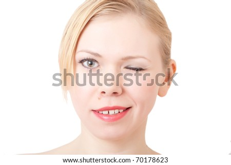 happy beautiful woman touching face and looking at camera winks - stock photo