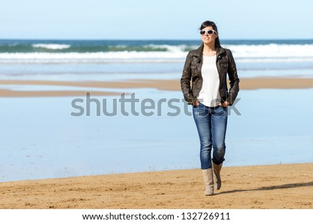 Happy beautiful woman walking on beach. Casual brunette girl taking a walk and relaxing on spring vacation. Copy space. - stock photo