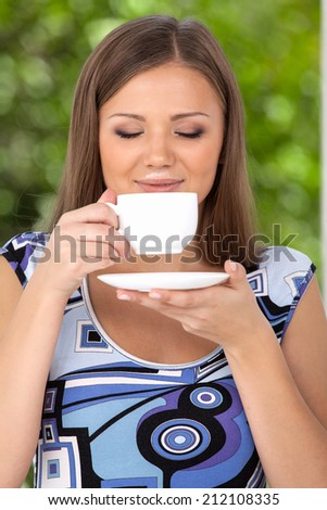 Happy beautiful woman with coffee cup in hands. front view of brunette drinking coffee in park outside