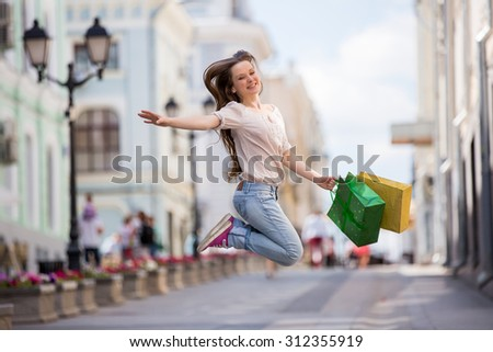 Happy beautiful woman with colorful shopping bags in hand cheerfully jumping in the air.  - stock photo