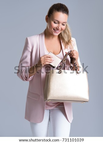 Happy beautiful woman with handbag and wallet in shopping - over white background