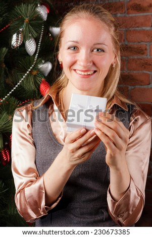 Happy beautiful woman with white gift box under the Christmas tree - stock photo
