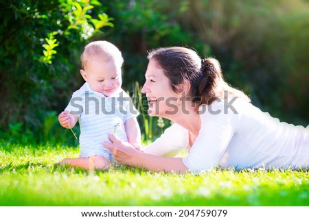 Happy beautiful woman, young mother playing with her adorable baby son, cute little boy, enjoying together a sunny warm day playing on the lawn in a summer garden - stock photo