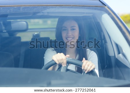 happy beautiful young brunette woman driving her car  - stock photo
