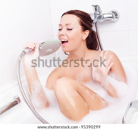 happy beautiful young brunette woman taking a relaxing bath with foam and singing - stock photo