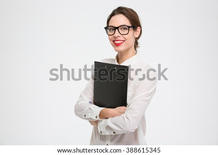 Happy beautiful young business woman standing and holding clipboard over white background - stock photo