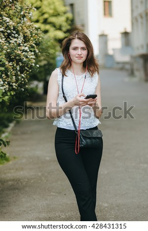 Happy beautiful young Caucasian girl with smart phone outdoors