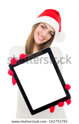 Happy beautiful young Caucasian woman with Santa hat and gloves showing tablet computer screen. Isolated screen and background. Copy space available.  - stock photo
