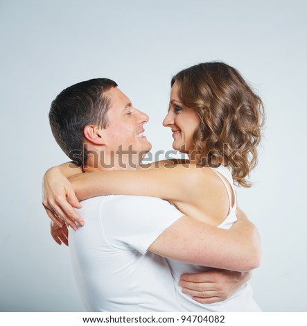 Happy beautiful young couple in love in white casual clothing. In the studio - stock photo