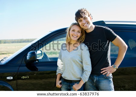 happy beautiful young couple standing near the car - stock photo