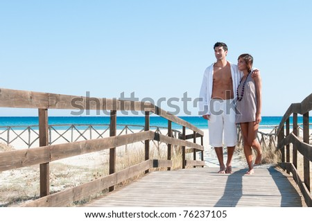 Happy beautiful young couple walking together at summer tropical beach - stock photo