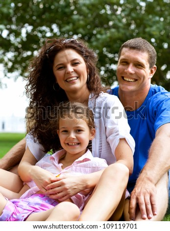 Happy beautiful young family sitting on the green grass. Three cheerful person - stock photo
