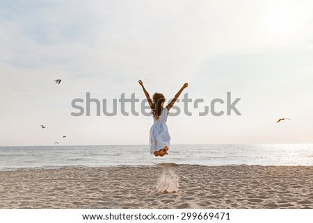 Happy beautiful young girl in a dress on the beach jumping for joy - stock photo