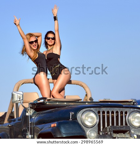 Happy beautiful young girls sitting in beach truck car in sunglasses on sunny summer day - stock photo