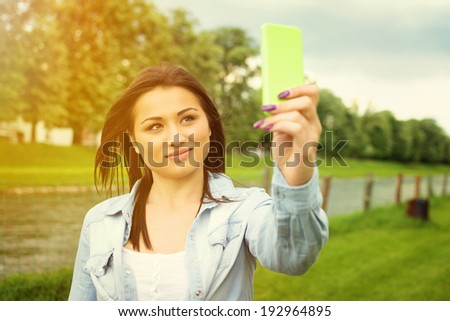 Happy beautiful young mixed race woman taking a selfie photo in park with green smart phone. Millennial teenager portrait. - stock photo