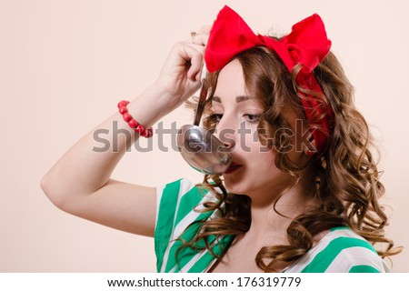 Happy beautiful young pinup woman with ladle - stock photo