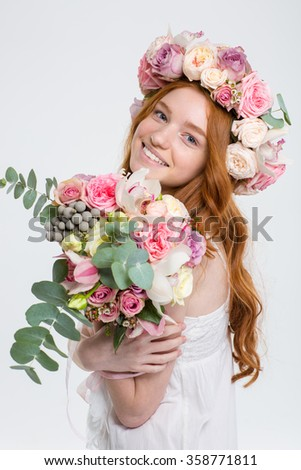 Happy beautiful young redhead woman in roses wreath with bouquet of flowers over white background - stock photo