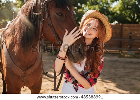 Happy beautiful young woman cowgirl in hat standing and hugging her horse