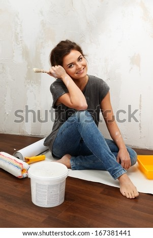 Happy beautiful young woman doing wall painting - stock photo