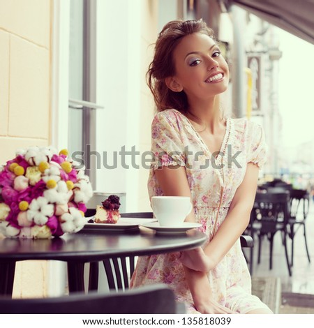 Happy beautiful young woman drinking coffee. Outdoors - stock photo