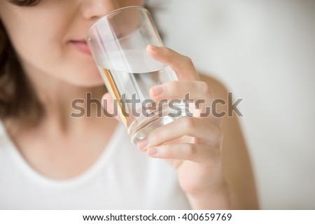 Happy beautiful young woman drinking water. Smiling caucasian female model holding transparent glass in her hand. Closeup. Focus on the arm - stock photo