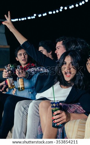 Happy beautiful young woman holding drink and laughing lying over her group of friends sitting in a outdoors party. Friendship and celebrations concept. - stock photo