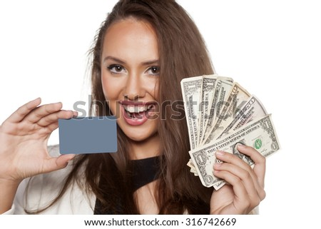 happy beautiful young woman holding money and a credit card - stock photo