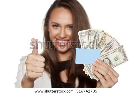 happy beautiful young woman holding money and a credit card and showing thumbs up - stock photo