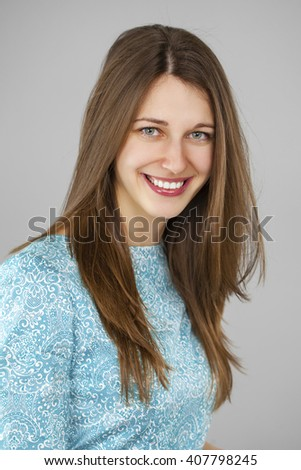 Happy beautiful young woman in a turquoise dress on a gray background. Studio portrait