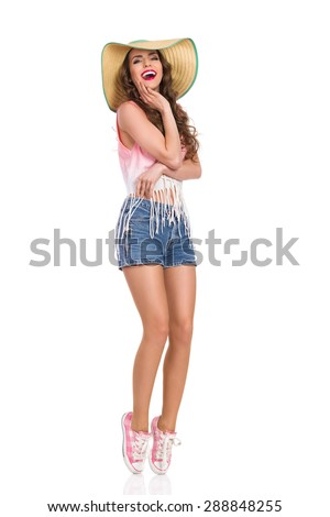 Happy beautiful young woman in straw hat, jeans short, pink top and sneakers standing on tiptoe. Full length studio shot isolated on white. - stock photo