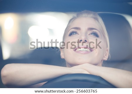 Happy beautiful young woman leaned on the steering wheel of the car - stock photo