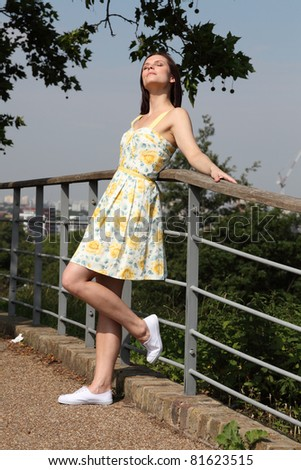 Happy beautiful young woman leans on fence in park, head upturned with eyes closed enjoying the sunshine. She is wearing yellow summer dress and white deck shoes. - stock photo