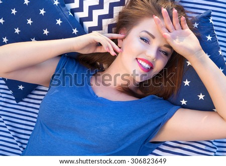 Happy beautiful young  woman lying in bed - stock photo