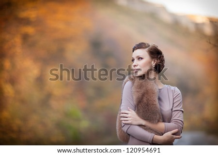 Happy beautiful young woman outdoors in autumn park  Enjoying the nature. Elegant rich girl posing at autumn nature with hairstyle and fur at sunset in park - stock photo