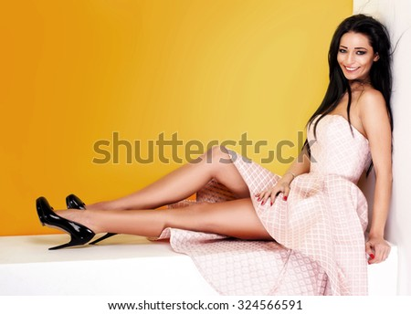 Happy beautiful young woman posing in studio, wearing elegant dress. Girl looking at camera. Fashion photo. - stock photo
