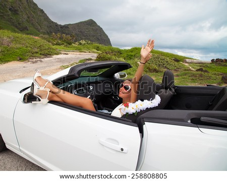 Happy beautiful young woman sitting in a sports car on beautiful summer day. Sexy woman's legs showing out of the car, enjoying freedom feeling happy on the Hawaii.  - stock photo