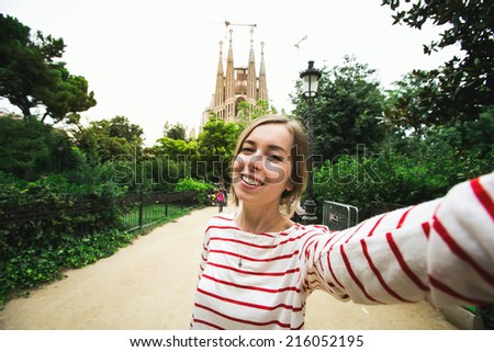 Happy beautiful young woman tourist smiling and taking selfie self-portrait in front of Sagrada Familia while traveling in Barcelona, Spain. - stock photo