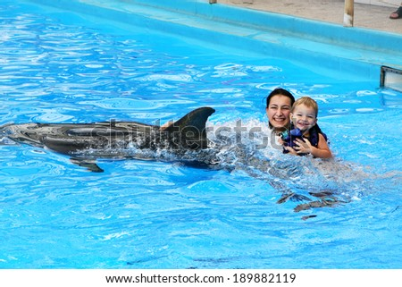 Happy beautiful young woman with a small child laughs and swims with dolphins in blue swimming pool on a clear sunny day - stock photo
