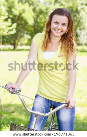Happy beautiful young woman with bicycle in the park. - stock photo