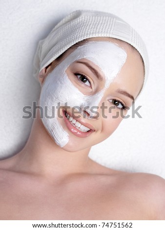 Happy beautiful young woman with cosmetic mask in a half of face
