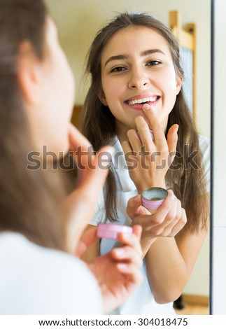 Happy beauty teenager applying lipstick in front of a mirror at home - stock photo